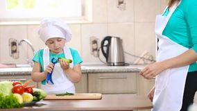 Mom teaches child to clean cucumber stock video
