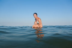 Mom teaches a child to swim Royalty Free Stock Image