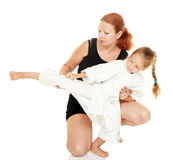 Mom teaches daughter dressed in a kimono karate kick Royalty Free Stock Photo