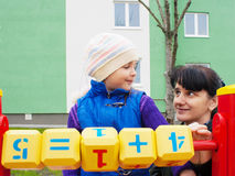Mom teaches daughter to be considered with wooden cubes. Mom teaches daughter to be considered at the playground with wooden cubes on spring day outside Stock Photography
