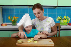 Mom teaches daughter to cut the potatoes Stock Photography