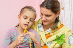 Mom teaches daughter to knit. Seven years Royalty Free Stock Images