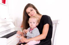 Mom teaches daughter to play the piano royalty free stock image