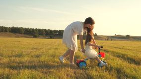 Mom teaches daughter to ride a bike. daughter and mother are playing in the meadow. Mother plays with her little stock video footage