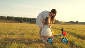 Mom teaches daughter to ride a bike. Mother plays with her little daughter. a small child learns to ride a bike. concept stock video footage