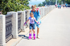 Mom teaches daughter to roller-skate stock photography