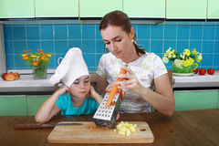 Mom teaches daughter  to rub carrot on a grater Royalty Free Stock Photos