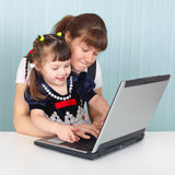 Mom teaches daughter to use laptop Royalty Free Stock Photos