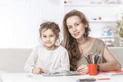 Mom teaches five year old daughter to draw with pencils. Mother and five year old daughter draw. children`s creativity. development of the child Royalty Free Stock Images