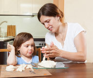 Mom teaches the girl to mold dough figurines Royalty Free Stock Photography