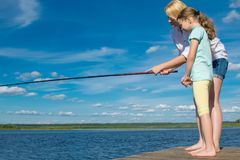 Mom teaches her daughter to fish, outdoors, standing on the pier, against the blue sky stock photography