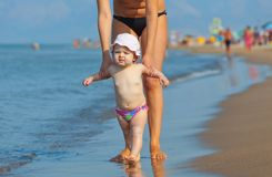 Mom teaches her daughter to walk to the beach. First steps with the help of the mother Royalty Free Stock Images