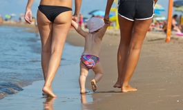 Mom teaches her daughter to walk to the beach. First steps with the help of the mother Stock Photos