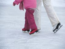 Mom teaches her little daughter to skate on the rink on a winter day. royalty free stock photos