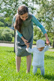 Mom teaches her little daughter to walk, hands Royalty Free Stock Image