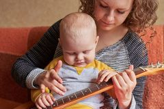 Mom teaches her little son to play the guitar. Early child development stock photos