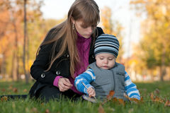 Mom teaches her son in the autumn park Royalty Free Stock Photography