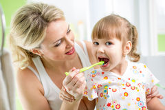 Mom teaches kid teeth brushing royalty free stock photos