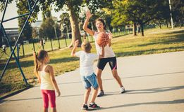 Mom teaches kids to have a sporting life. Mother with children on playground playing basketball stock photo