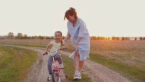 Mom teaches little daughter to ride bike at sunset outdoors nature