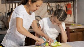 Mom teaches and shows her daughter how to cut apple on small pieces. Family cooking together, portrait of mom teaches and shows her teen girl daughter how to stock video footage