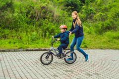 Mom teaches son to ride a bike in the park royalty free stock image