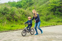 Mom teaches son to ride a bike in the park stock photography