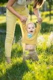Mom teaches son walking grass Stock Image