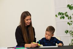 Mom teaches young boy son to draw markers at the table. Mom teaches young boy son to draw flamasterami for table royalty free stock photography