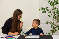 Mom teaches young boy son to draw markers at the table. Mom teaches young boy son to draw flamasterami for table royalty free stock photos