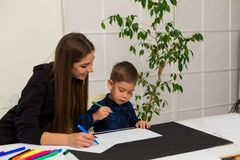 Mom teaches young boy son to draw markers at the table. Mom teaches young boy son to draw flamasterami for table royalty free stock image