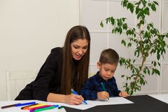 Mom teaches young boy son to draw markers at the table. Mom teaches young boy son to draw flamasterami for table royalty free stock photo