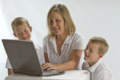 A Mom teaching 6 years olds how to use a laptop Stock Photo
