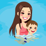 Mom Teaching Baby Boy Swimming. Beautiful brunette mom at swimming pool teaching her baby boy how to swim Royalty Free Stock Image