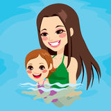 Mom Teaching Baby Girl Swimming. Beautiful brunette mom at swimming pool teaching her baby girl how to swim Royalty Free Stock Photo