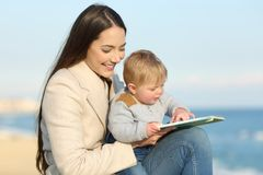 Mom teaching and baby learning reading a book Stock Images