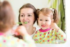 Mom teaching child teeth brushing. Mom teaching daughter child teeth brushing in bathroom royalty free stock image