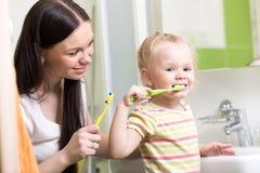 Mom teaching child teeth brushing Stock Photography