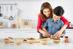 Mom is teaching children to cook food from vegetables in the kitchen stock photo