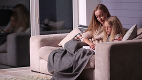 Mom teaching daughter to read at home stock video