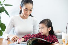 Mom is teaching her daughter to read a book royalty free stock photography