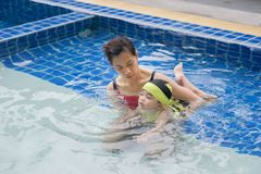 Teaching swim. Mom is teaching her daughter to swim in the pool royalty free stock image
