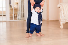 Mom teaching her son`s first baby steps indoors Stock Photo