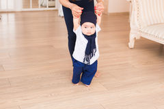Mom teaching her son`s first baby steps indoors Stock Image