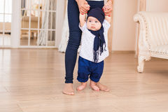 Mom teaching her son`s first baby steps indoors Stock Photos