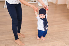 Mom teaching her son`s first baby steps indoors Stock Photography