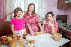 Mom teaching her two daughters cooking on the kitchen. Stock Photography