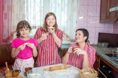 Mom teaching her two daughters cooking on the kitchen. Stock Photo