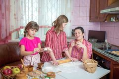 Mom teaching her two daughters cooking on the kitchen. Royalty Free Stock Photos