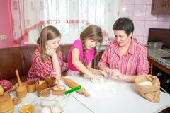 Mom teaching her two daughters cooking on the kitchen. Royalty Free Stock Image